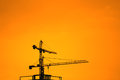 Industrial construction cranes silhouettes on orange background Royalty Free Stock Image