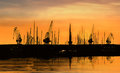 Industrial cranes shown as silhouettes sunset Royalty Free Stock Photo
