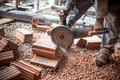 Industrial engineer working on cutting bricks at construction site, using a grinder, electrical mitre saw with sharp blade Royalty Free Stock Photo