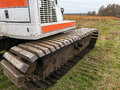 Industrial excavating machine side view of an on a grassy field Royalty Free Stock Photos