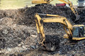 industrial excavator digging into trash at urban dumping grounds Royalty Free Stock Photo