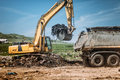 Industrial excavator using scoop and moving earth and trash at garbage dumping site. Royalty Free Stock Photo
