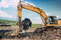 Industrial excavators and heavy duty machinery working on garbage dump site. Royalty Free Stock Photo