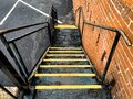 Industrial fire escape safety alley stairs steps with bright yellow caution stripes next to retro red brick building wall Royalty Free Stock Photo