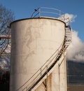 Industrial fuel oil storage tank in haines alaska with blue sky puffy clouds and a crow sitting on the top railing Royalty Free Stock Images