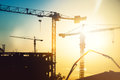 Industrial heavy duty construction site with tower cranes and building silhouettes Royalty Free Stock Photo