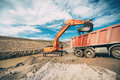 Heavy duty machinery, details of excavator building highway and loading dumper trucks Royalty Free Stock Photo