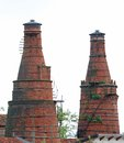 Industrial heritage site with a historic building and the old red brick furnaces with high chimneys Royalty Free Stock Photos