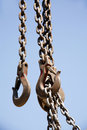Industrial hook with chains against a bright blue sky Royalty Free Stock Photo