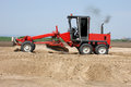 Industrial machine builds a new highway moving sand and gravel building Royalty Free Stock Image