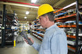 Industrial manufacturing inventory warehouse worke a worker is using a hand held scanner for management control in an factory Royalty Free Stock Images