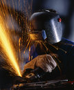 Industrial metalworker with an electric drill cutting a piece of metal and producing lot of sparks Stock Photos