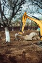 Industrial mini excavator scoop moving earth and doing landscaping works Royalty Free Stock Photo