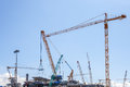 Industrial plants are currently under construction with many tower cranes and worker Royalty Free Stock Images