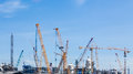Industrial plants are currently under construction with many tower cranes and worker Stock Image