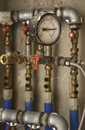 Industrial pressure meter and water pipes Royalty Free Stock Photo