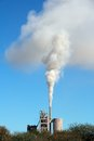 Industrial smog smoke from an plant drifting in the wind against a blue sky Royalty Free Stock Photography