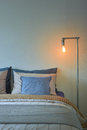 Industrial style reading lamp and blue pillows on modern bedroom Royalty Free Stock Photo