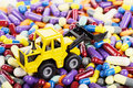 Industrial tractor toy load pills and tablets installation on the theme of modern medicine Stock Photography