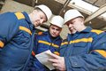 Industrial workers on house building plant three engineer chief discussing enterprise development in Stock Photography