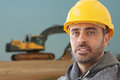 Industrial workman in a hat hat handsome young builder or or safety helmet against backdrop showing large mechanical excavator Royalty Free Stock Photos