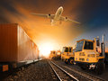 Industry container trainst running on railways track plane cargo flying above and ship transport in import export yard Royalty Free Stock Images