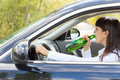 Inebriated female driver drinking alcohol directly from the bottle as she steers her car along the road posing a danger to others Royalty Free Stock Photo