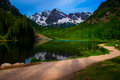 Infamous maroon bells of aspen colorado with walking path and reflection a perfect early summer day morning sunrise sunshine Royalty Free Stock Images