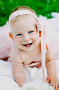 Infancy and age concept . beautiful happy baby in pink dress in the park playing Royalty Free Stock Photo