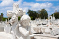 Infant angel praying and christian cross with a diffused cemetery background Royalty Free Stock Image