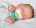 Infant baby boy sleeping with pacifier Stock Images