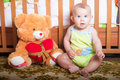 Infant baby playing on the floor at home with teddy bear Royalty Free Stock Image