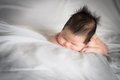 Infant boy sleeping on white bed Stock Photography