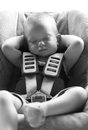 Infant boy sleeps peacefully secured with car seat belts while in the Stock Photo