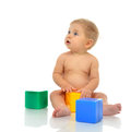 Infant child baby boy toddler playing holding green blue yellow bricks in hands on a floor on and looking up isolated a white Royalty Free Stock Photography