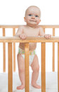 Infant child baby boy toddler in wooden bed standing diaper on white background Stock Photography
