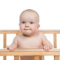 Infant child baby boy in wooden bed looking up on white background Royalty Free Stock Image