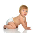 Infant child baby girl kid in diaper crawling happy looking at t Royalty Free Stock Photo