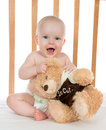 Infant child baby girl shouting in diaper with teddy bear a bed on white background Stock Images