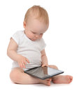 Infant child baby toddler sitting and typing digital tablet mobi mobile computer isolated on a white background Stock Photo