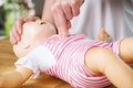 Infant cpr two finger cvompression woman showing on training doll performing chest compression Royalty Free Stock Images