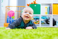 Infant crawling on the green carpet in child room Stock Images