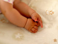 Infant hands of baby in the foreground on cradle background Royalty Free Stock Photo