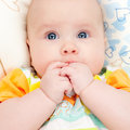 Infant with hands in mouth Stock Image