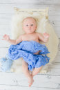 Infant lies in a small baby bed wrapped blue soft material on wooden floor Stock Photos