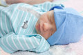 Infant sleeping wearing a blue hat on his back Royalty Free Stock Image