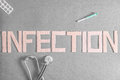 Infection a stethoscope pills and a disposable syringe on a dark background with the word made out of cardboard for your medical Royalty Free Stock Images