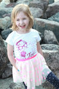Infectious laughter blonde little girl walks on the beach Royalty Free Stock Image