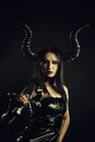 Infernal warrior horned gothic girl in black latex dress posing over dark background with sword Stock Photo