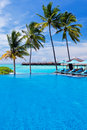 Infinity pool with umbrellas and palm trees Royalty Free Stock Image